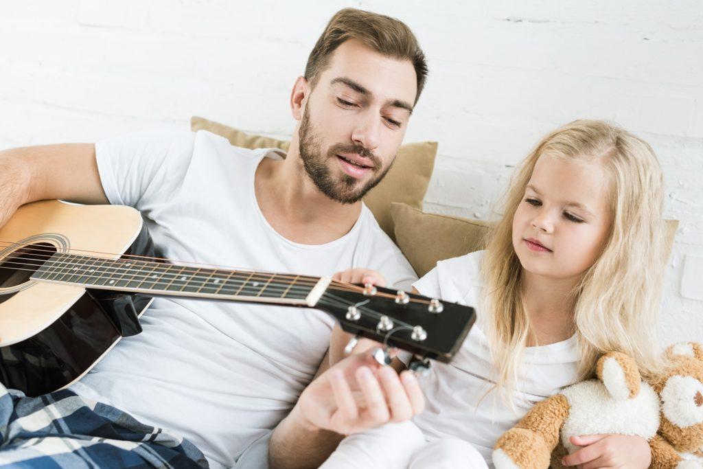 Kind leert gitaar spelen