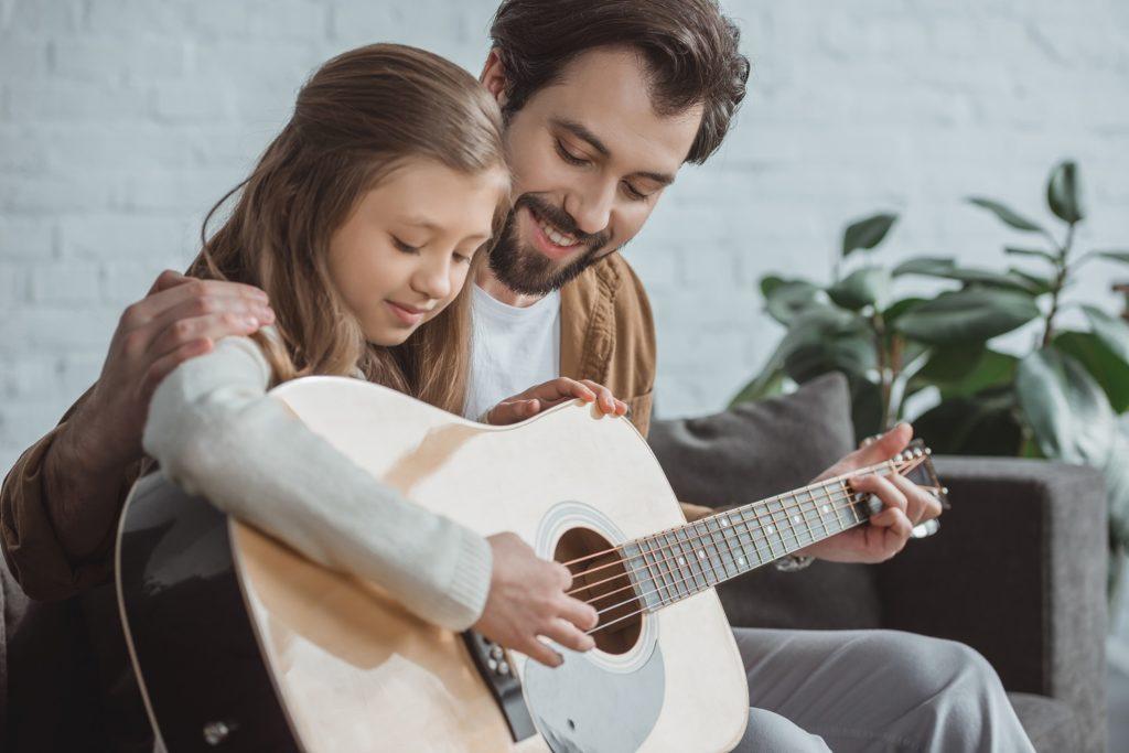 Kind leert gitaar spelen met vader